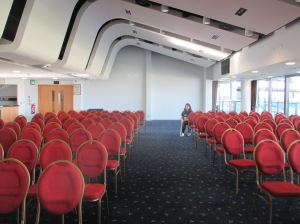 A long white room with a sloped ceiling and blue carpet. There are rows of empty red chairs.