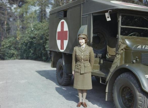 A dark-haired woman of 19 in a military uniform stands in from of a green truck with a large red cross on the right face.