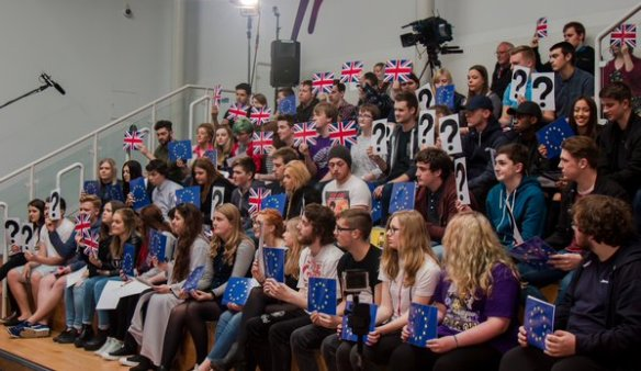 A crowd of adolescents on stepped seating. They hold up cards with Union Flags, EU Flags or Question Marks.