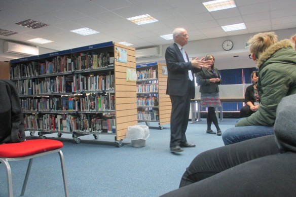 A modern library - a bald man stands before a crowd of adolescents.