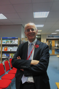 A bald man in a suit with a poppy and lanyard smiles while crossing his arms.