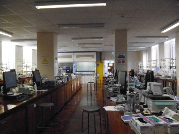 A laboratory, with polished wooden furnishings a scattering of computers and machinery.
