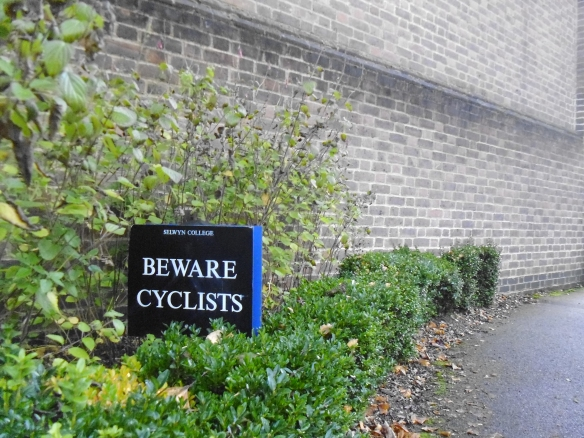 """A bush-lined path with a black sign bearing the words """"Selwyn College Beware Cyclists"""""""