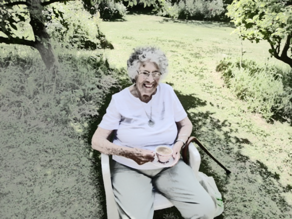 An old woman with thick white hair sits in a sunny garden with a cup of tea.