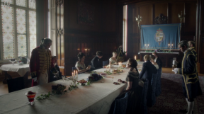 A wood-panelled dining room with a long table covered by a white sheet. Guests in luxurious costume. On the back wall is a hanging cloth printed with the arms of The Viscount Palmerston.